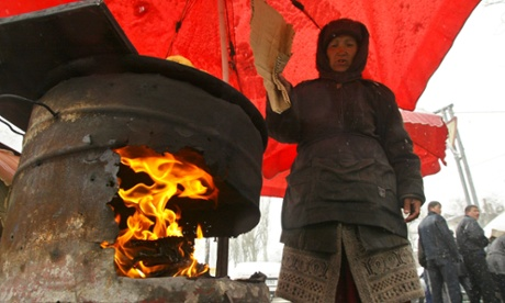 A street vendor keeps a fire in a makeshift oven to warm traditional bread for sale at a city market in Bishkek, Kyrgyzstan, 2005.