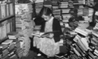 A young girl reading in a cluttered corner of Foyles bookshop, London.
