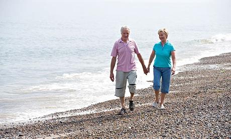 mature couple walking on shingle beach. Image shot 2009. Exact date unknown.