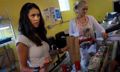 A marijuana saleswoman bags up a sale for a customer at Dr Reefer's marijuana dispensary at the University of Colorado in Boulder, Colorado.