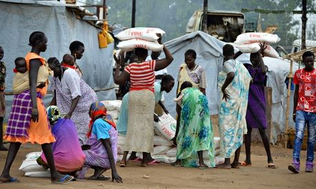 Women carry sacks of maize flour at a food distribution point in Juba, South Sudan