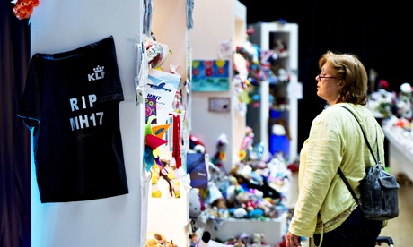 A traveller at Amsterdam's Schiphol airport looks at tributes to victims of the Malaysia Airlines flight MH17 crash.