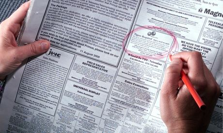 Person looking at job vacancies in a newspaper