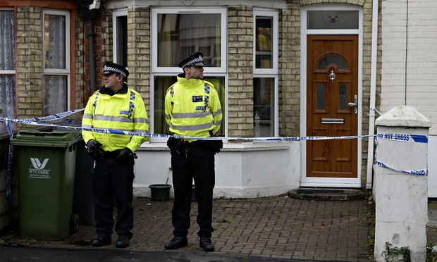 Police officers stand outside a house in High Wycombe after a series of raids in which the three accused were arrested. Photograph: Andrew Matthews/PA