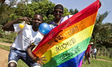 Ugandan men hold a rainbow flag at the annual gay pride festival in Entebbe, Uganda
