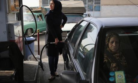 A woman fills her car with petrol in Shahinshahr, Iran.
