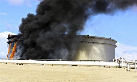 Black smoke billows out of an oil tank
