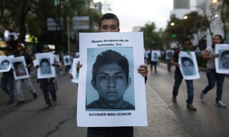 A demonstrator carries a photograph of Alexander Mora Venancio during a march in Mexico City.