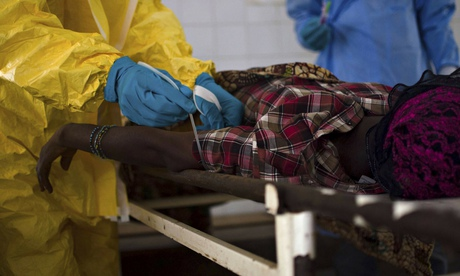 Medical staff take a blood sample from a suspected Ebola patient in Sierra Leone