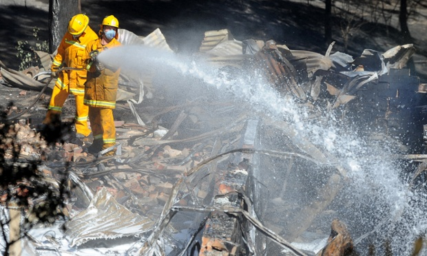 Members of the CFA put out smothering fires after a fast moving bushfire took out at least three homes in the Melbourne north east suburb of Warrandyte.