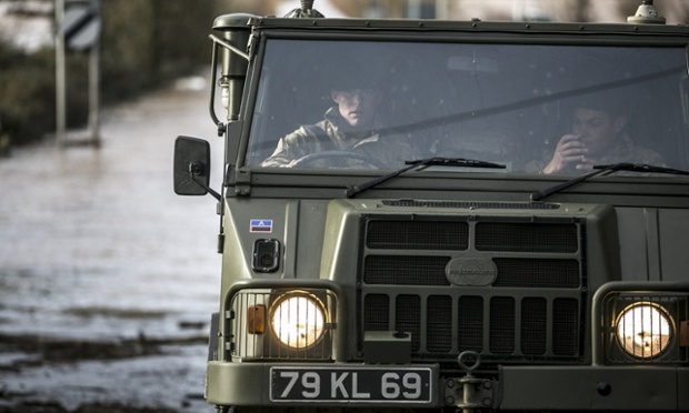 Royal Marines drive a 4x4 vehicle through  Burrowbridge on the Somerset Levels.