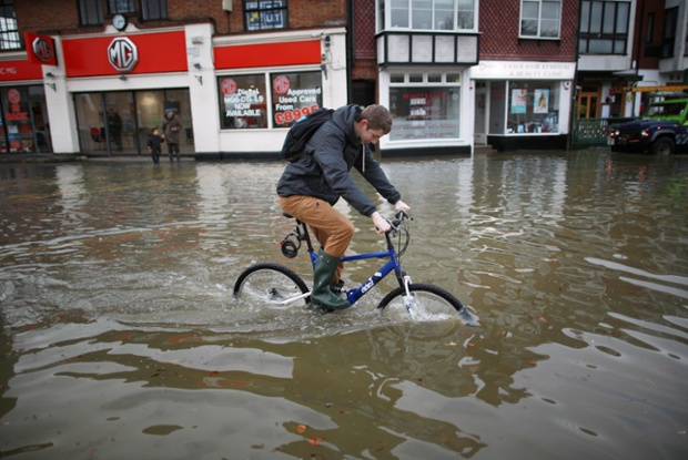 A man attempts to cycle through flood water in Datchet, England.
