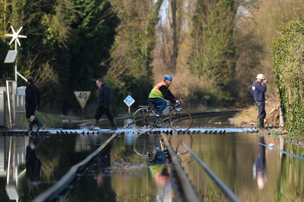 A cyclist crosses the flooded train tracks in Datchet in Berkshire