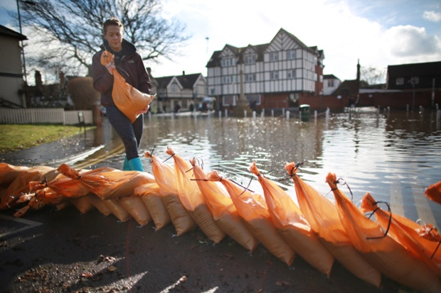 A resident of Datchet builds a sandbag flood wall to protect her home.