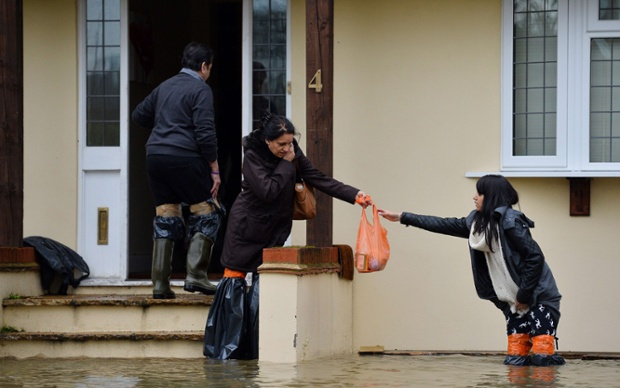 Residents wearing homemade waders evacuate their home in Wraybury, Berkshire.