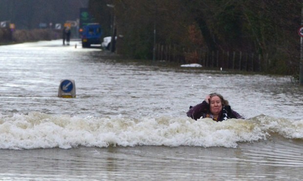 A woman falls over in a flooded street in Old Windsor, Berkshire.