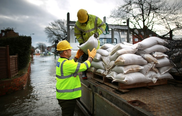Electricity workers unload sandbags to protect a sub station in Datchet, Berkshire.