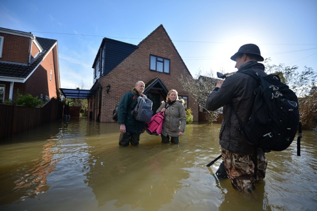 Residents speak to a TV journalist in a flooded street in Wraysbury, Berkshire.