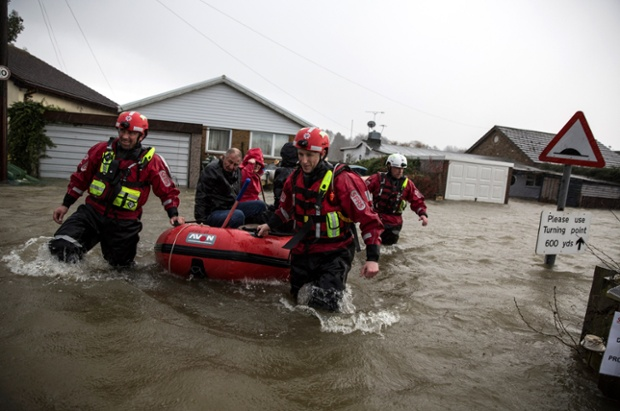 A Fire and Rescue crew help evacuate residents from flooded homes in Walton-on-Thames.