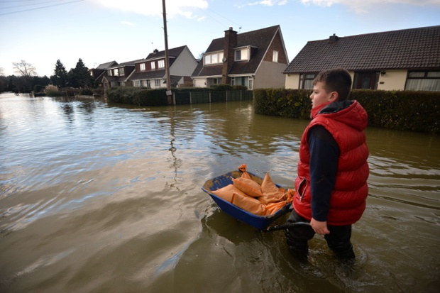 A boy in Wraysbury, Berkshire helps move sandbags.
