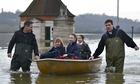 School children are ferried by boat after the Thames burst its banks in Old Windsor