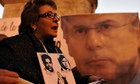 A woman remembers victims of Argentina's fascist regime before a picture of judge Baltasar Garzón