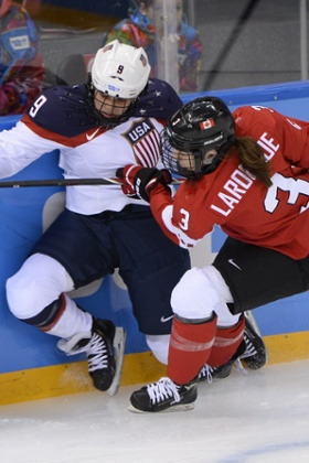 Canada's Jocelyne Larocque (R) hits US star Megan Bozek during their Women's Ice Hockey Group A match