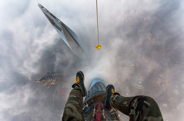 Vitaly Raskalov's feet dangling from on top of the Shanghai tower, China.