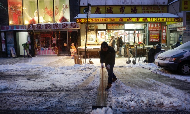 A man clears snow in front of the Gold Shing Market in Chinatown, New York.