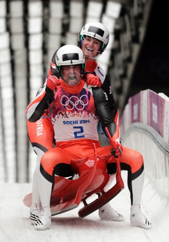 The doubles team of Andreas Linger and Wolfgang Linger from Austria celebrate in the finish area after their final run to win the silver medal during the men's doubles luge.