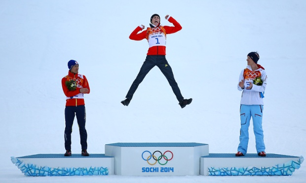 Gold medalist Eric Frenzel of Germany jumps in celebration alongside during the medal ceremony for the 10km Cross Country event.