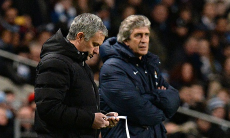Chelsea's Jose Mourinho looks at a notepad next to the Manchester City manager Manuel Pellegrini