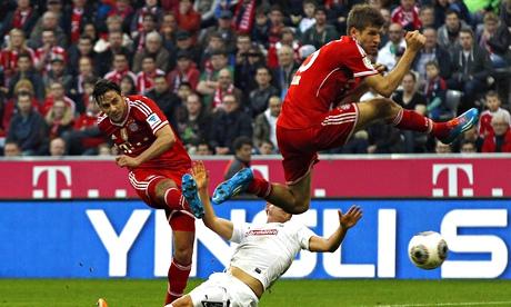 Bayern Munich's Claudio Pizarro, left, scores his side's fourth goal against Freiburg