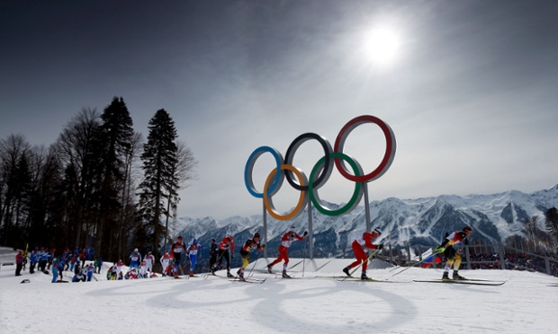The sun begins to descend in the sky as the field passes the Olympic rings in the men's 15km + 15km skiathlon.