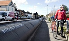 A man pushes his bicycle past the 'Chertsey Sausage' flood barrier