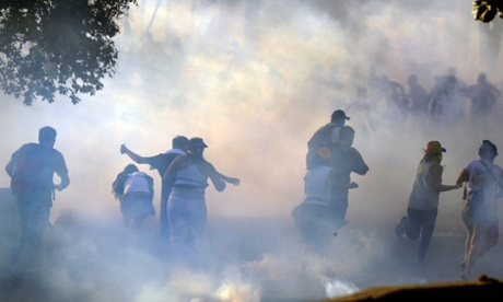 Students flee after the National Guard fires tear gas  in Caracas on Sunday.