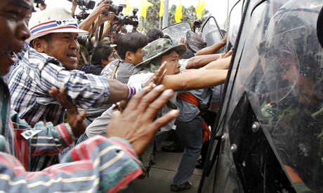 Farmers push against riot police during a protest in Bangkok