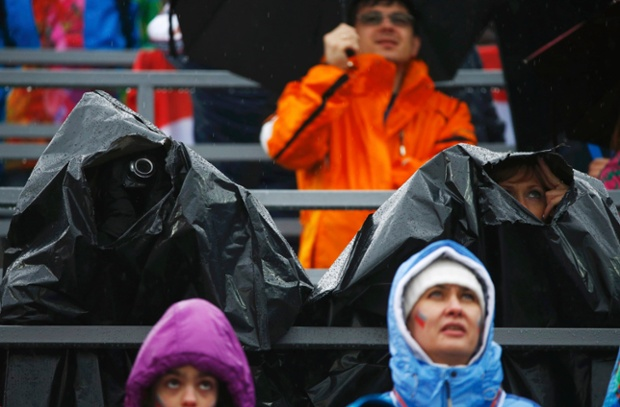 Spectators peer through bin bags to watch the large hill ski jumping.