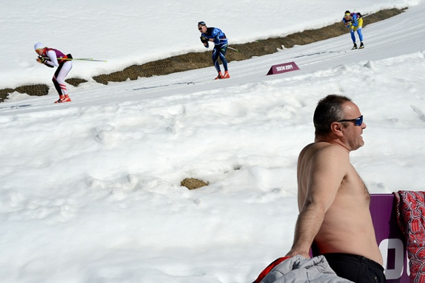 This cha`p seems more interested in sunbathing than the men's cross-country skiing behind him.