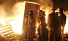 Anti-government protesters gather at a barricade near a fire during clashes with Interior Ministry members and riot police in central Kiev during the early hours of Wednesday.