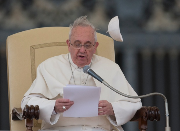 A gust of wind blows away Pope Francis' cap as he delivers his message.