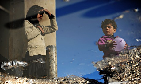 A Syrian internally displaced woman and child are reflected in a puddle of water in a refugee camp