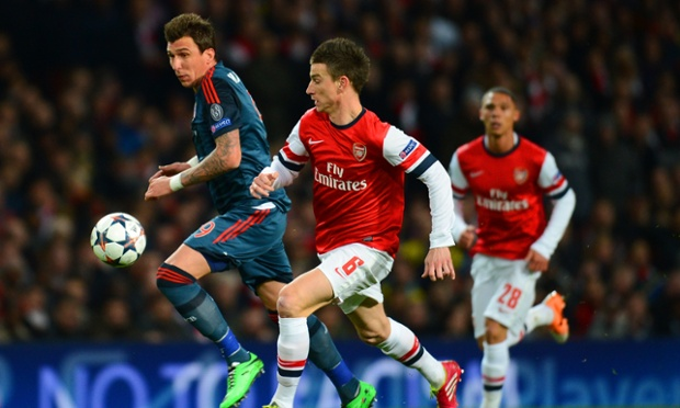Arsenal's Laurent Koscielny battles for the ball with Mario Mandzukic of Bayern Munich.