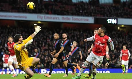 Alex Oxlade-Chamberlain calmly knocks the ball over Julian Speroni to score Arsenal's first goal.