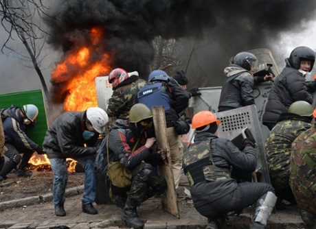Anti-government protesters try to shelter behind their shields during clashes with police in the center of Kiev.