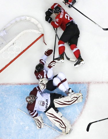 Switzerland's Nino Niederreiter crashes into Latvia's Oskars Bartulis and goalie Edgars Masalskis, causing the goal net to come off its moorings.
