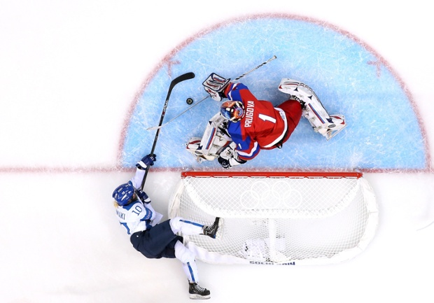 Linda Valimaki of Finland tries to scoop the puck past Anna Prugova of Russia.