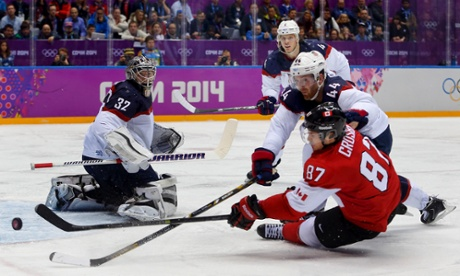 Canada forward Sidney Crosby shoots the puck against USA defenseman Brooks Orpik.