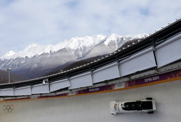 The team from Latvia, piloted by Oskars Melbardis, takes a curve during the men's four-man bobsleigh.