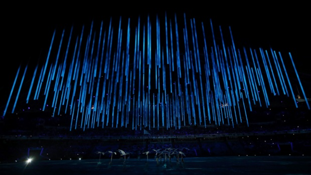 Performers hold up representations of birds as blue lights fill the stadium during the closing ceremony for the Sochi 2014 Winter Olympic Games.